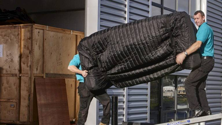Movers carrying a sofa onto a moving truck
